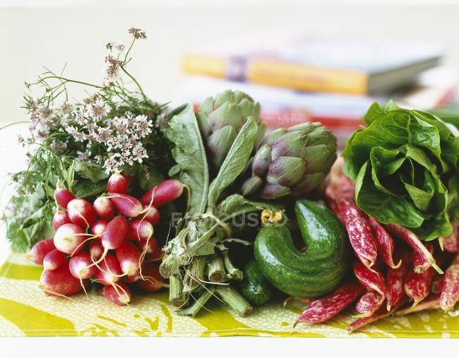 Arrangement of early vegetables on blurred background — Stock Photo