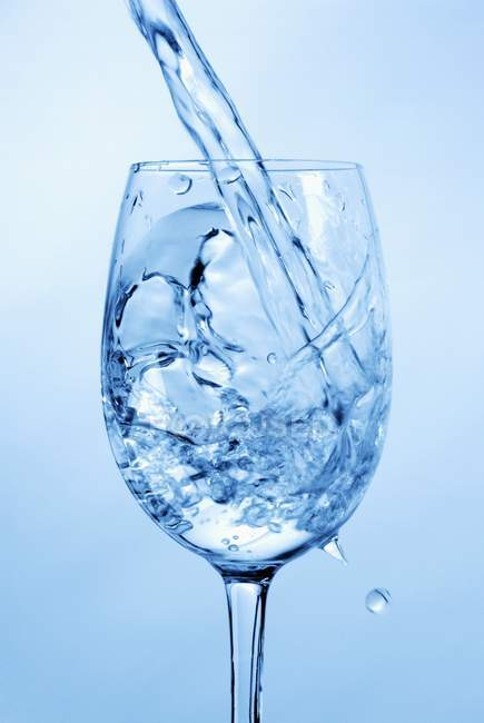 Agua chapoteando en vaso de agua - foto de stock