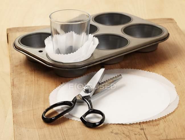 Principio di fare casi di cupcake fatti in casa con forno pergamena e cesoie rosa — Foto stock