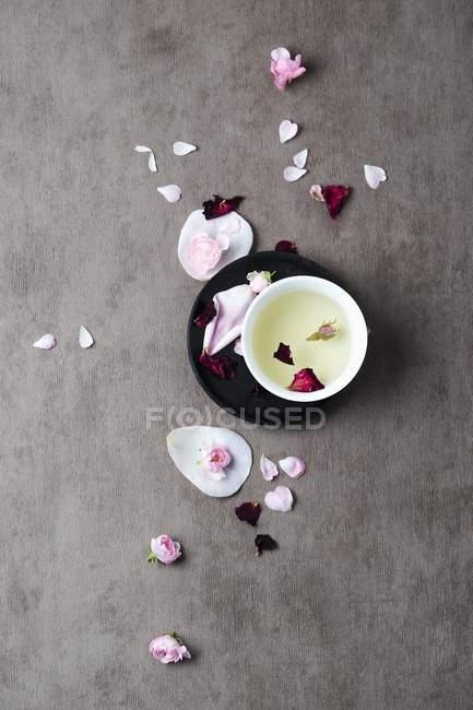 Верхний вид лепестков роз и чая на серой поверхности — стоковое фото