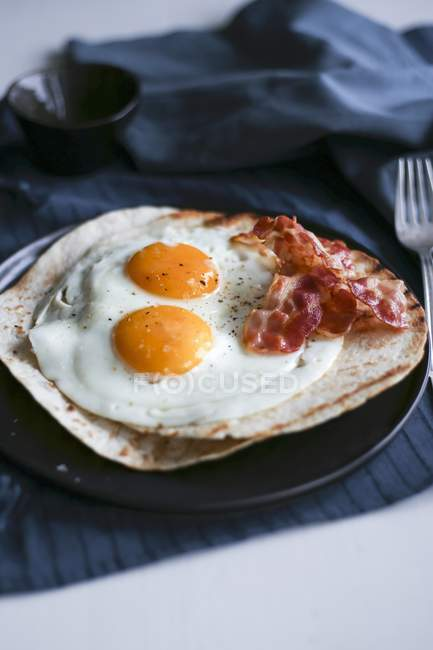 Breakfast tortilla with bacon and fried eggs — Stock Photo
