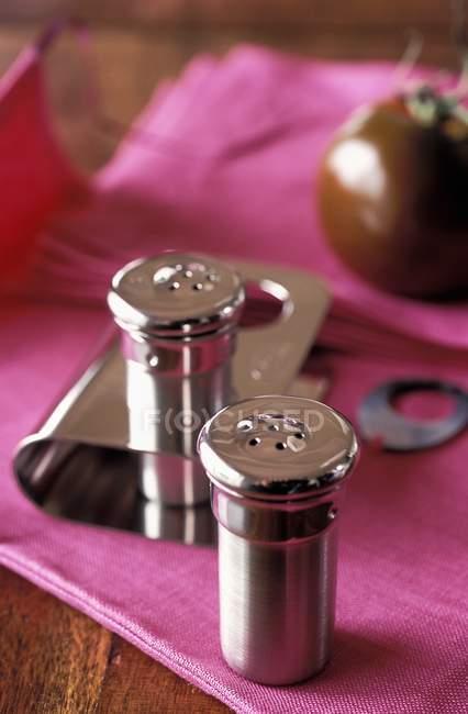 Vista de primer plano de las ollas de sal y pimienta con un tomate sobre tela rosa - foto de stock