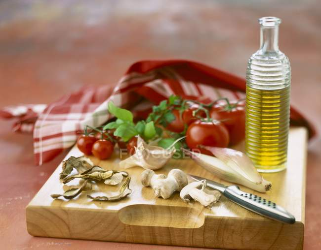 Composition of ingredients for Italian recipe on wooden chopping board with bottle and knife — Stock Photo