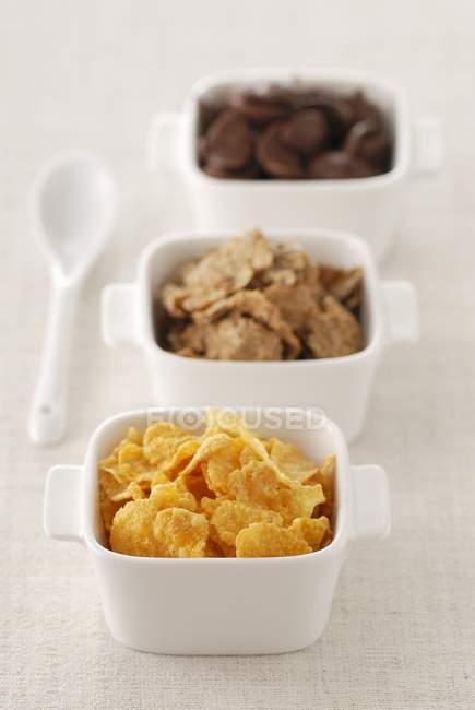 Vista de cerca de los cereales surtidos en tres tazones - foto de stock