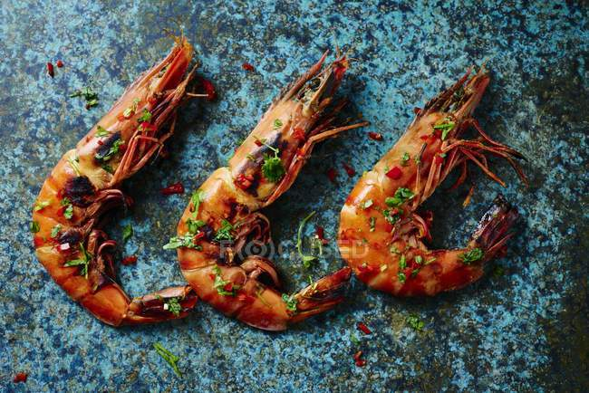 Prawns laying in a row on green marble surface — Stock Photo