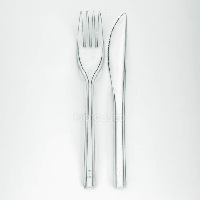 Closeup top view of knife and fork on white surface — Stock Photo