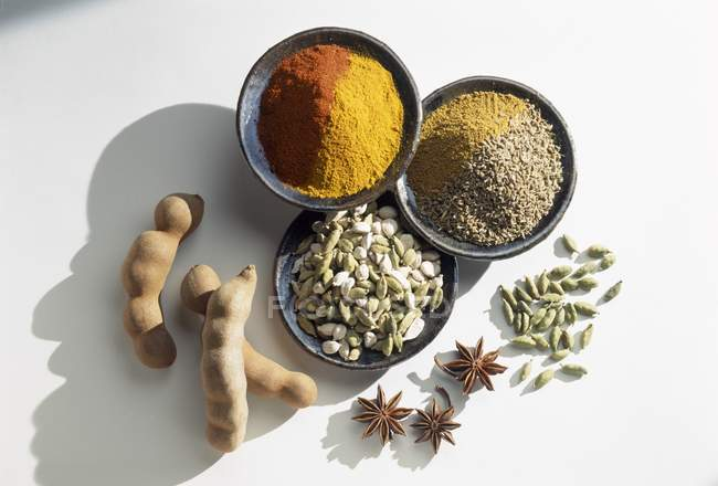 Selection of spices in bowls over white surface — Stock Photo