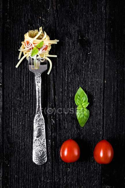 Italian pasta on fork with tomatoes and basil — Stock Photo
