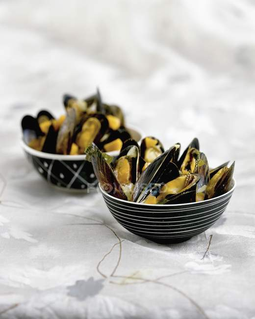 Spicy mussels in small black pots on table — Stock Photo