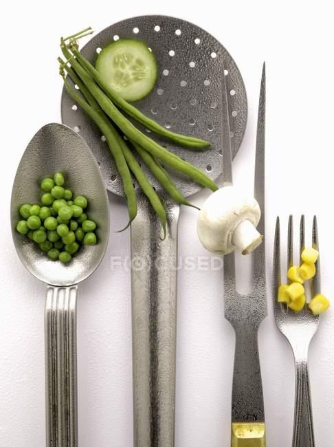 Состав с кухонными принадлежностями и овощами на белой поверхности — стоковое фото