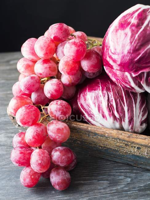 Closeup view of purple grapes bunch with radicchio — Stock Photo