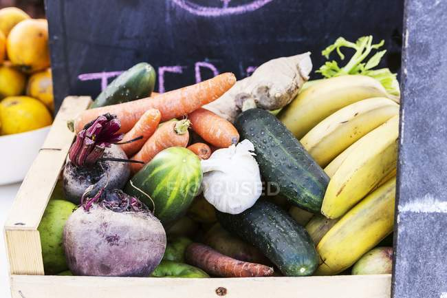 A wooden basket of different vegetables and fruits — Stock Photo