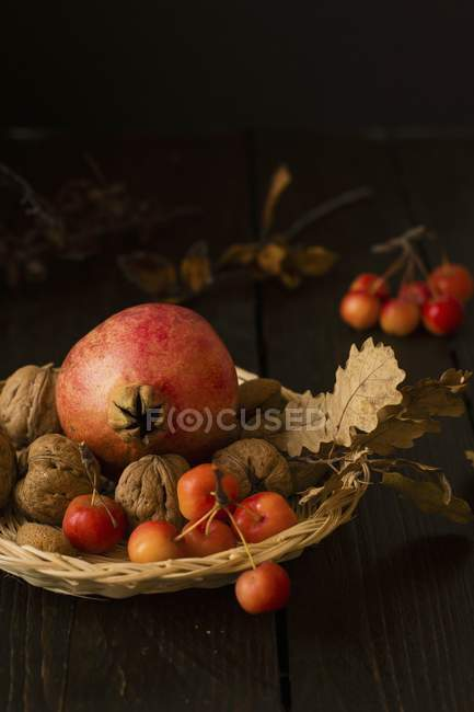 Closeup view of still life with pomegranate, walnuts and cherries — Stock Photo