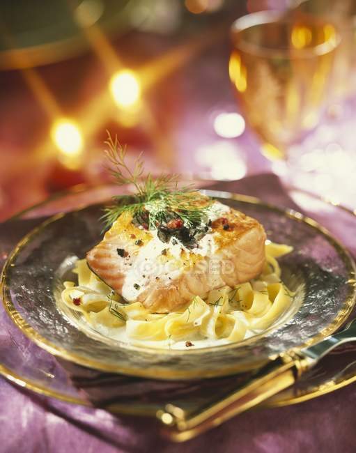 Thick piece of salmon with creamy tagliatelles — Stock Photo