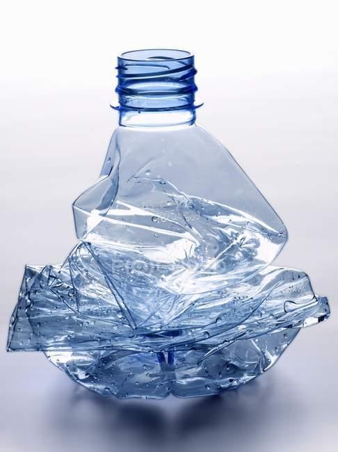 Vista close-up de garrafa de água de plástico esmagado e vazio — Fotografia de Stock