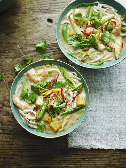 Top view of prawn Laksa with herbs in bowls — Stock Photo