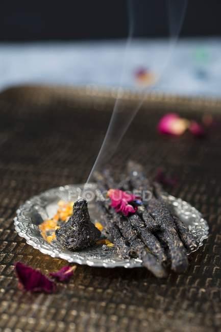 Vue rapprochée des bâtons d'encens faits maison et d'un cône en charbon de bois, résine et herbes et fleurs séchées — Photo de stock