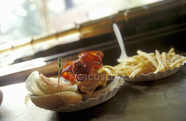 Hamburger and fries on plates — Stock Photo