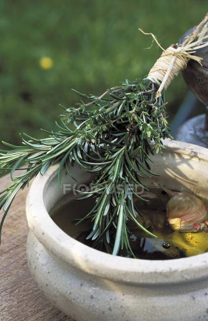 An oil marinade and a bunch of rosemary — Stock Photo