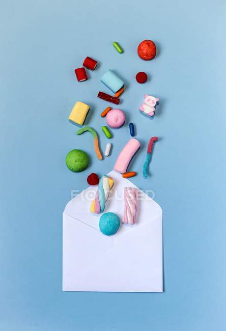 Top view of colorful sweets and envelope on light-blue surface — Stock Photo