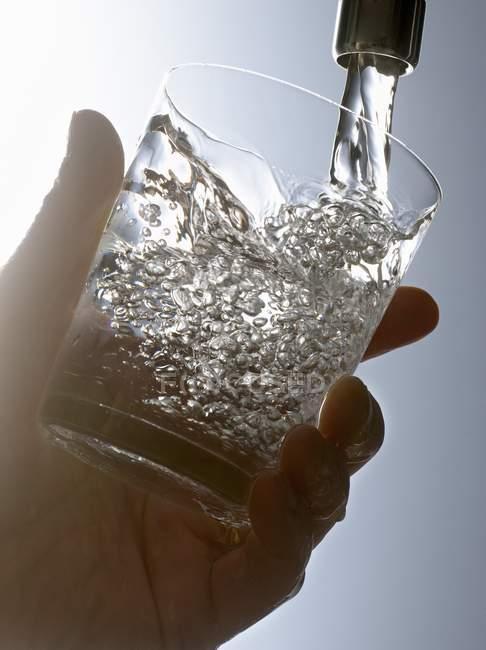 Крупным планом вид руки, заполнение стекла водопроводной водой — стоковое фото