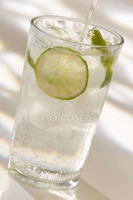 Closeup view of pouring sparkling water with slice of lemon — Stock Photo