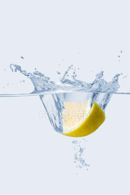 Lemon wedge falling in water — Stock Photo