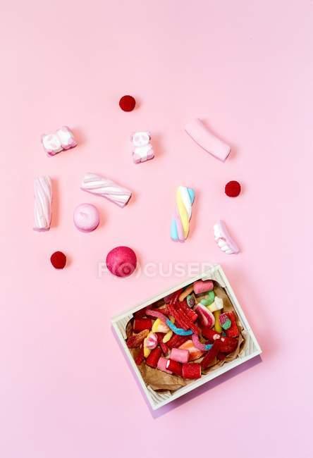 Vista superior de caramelos de colores y caja en la superficie rosa - foto de stock