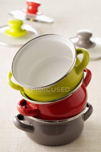 Vista de cerca de platos de cazuela de colores en la pila - foto de stock