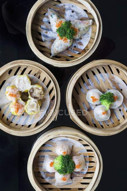 Top view of various Chinese steamed dumplings in bamboo steaming baskets — Stock Photo