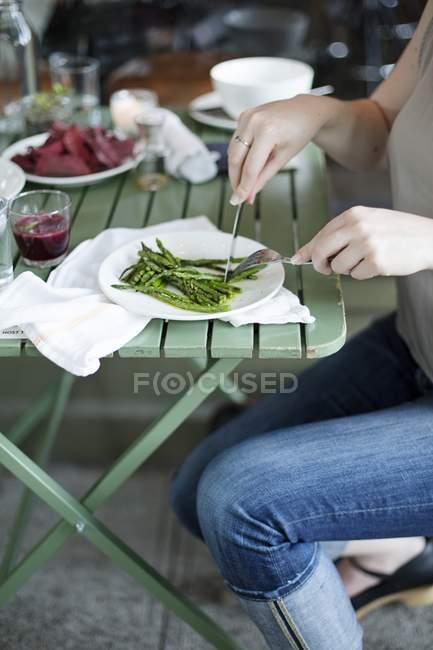 Женщина ест зеленую спаржу — стоковое фото