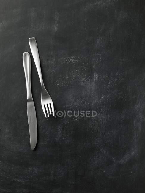 Vista superiore del coltello e forchetta su superficie nera — Foto stock