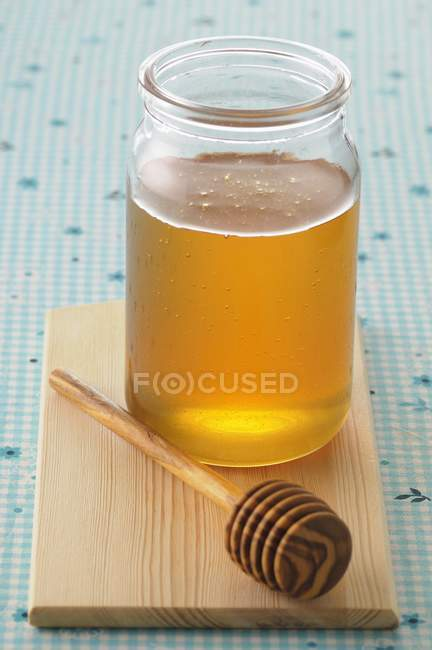 Pot of honey and wooden spoon — Stock Photo