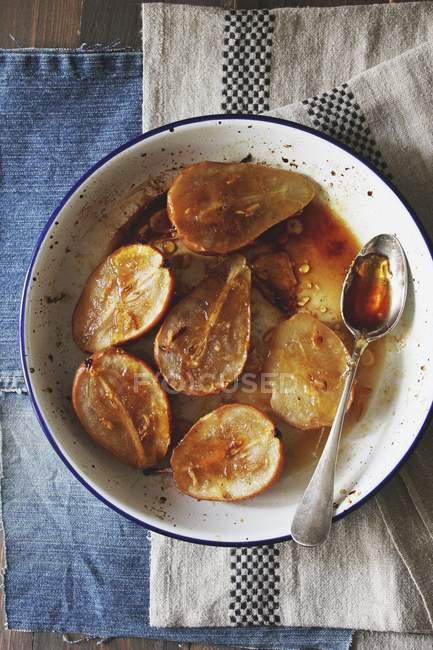 Vista superior de las peras en rodajas con salsa de caramelo y la cuchara en el tazón de fuente - foto de stock