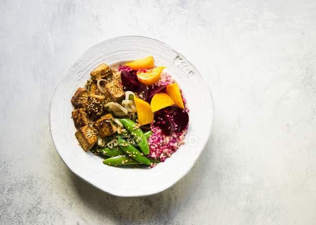 Barbabietole sottaceto dorate e rosse condite con quinoa, condite con tofu grigliato e piselli alla griglia — Foto stock