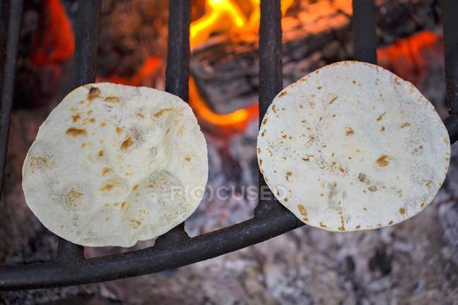 Closeup view of two Tortillas on a fire grate — Stock Photo