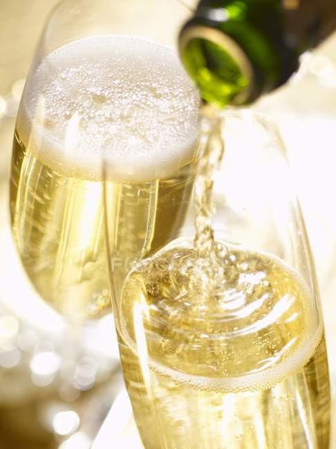 Розливом в стакан шампанське — стокове фото