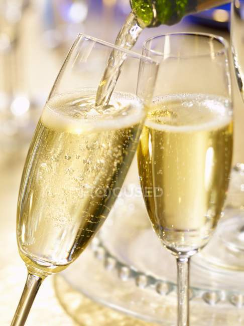 Champagne glasses and pouring champagne — Stock Photo