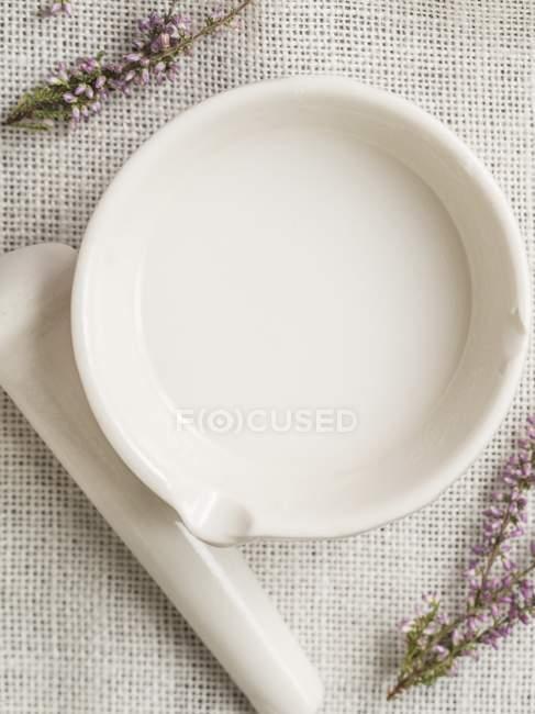 Крупним планом подання кокосового масла в ступці з маточкою і лаванди на тканині — стокове фото
