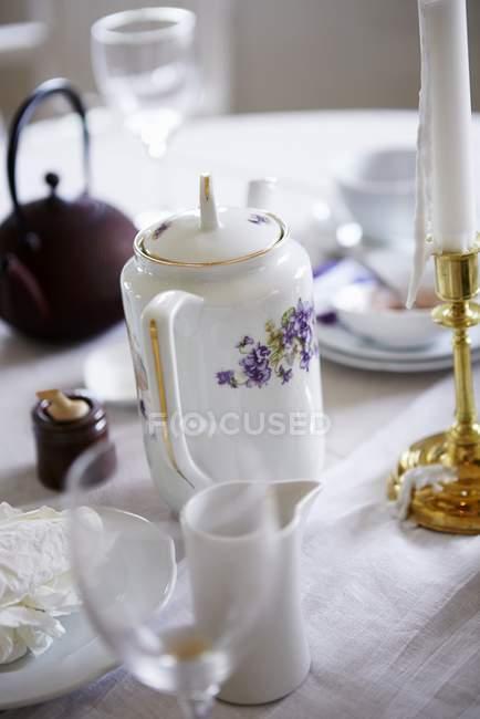 Vista de closeup de louças diferentes com vela na toalha de mesa branca — Fotografia de Stock