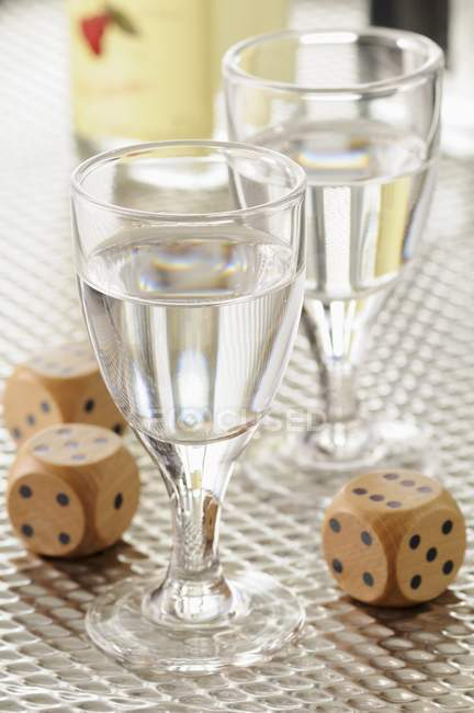 Closeup view of Eau-de-vie in glasses and dices — Stock Photo