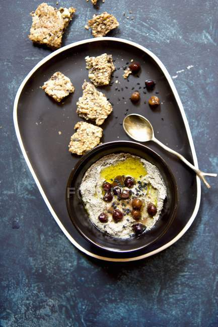Hummus with black chickpeas and sesame seeds on black plate — Stock Photo