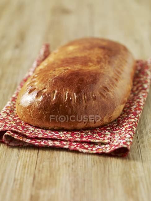 Крупним планом вид Fallue хліба на квітковим малюнком складеному рушник і дерев'яні поверхні — стокове фото