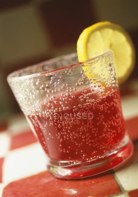 Vue rapprochée de boisson pétillante rouge avec tranche de citron en verre — Photo de stock