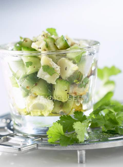 Chilled diced cod and cucumber with coriander in glass — Stock Photo