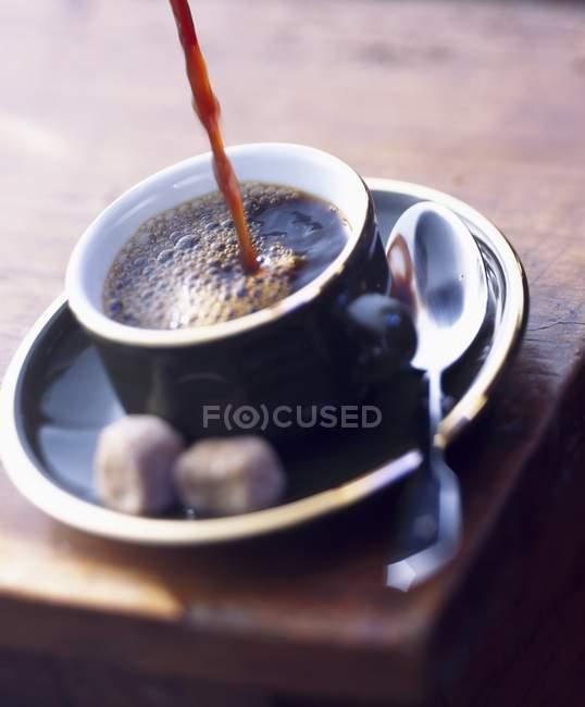 Verter el café en la taza - foto de stock