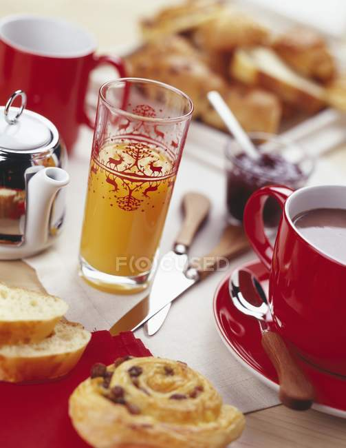 Continental breakfast with dishes and glasses over table — Stock Photo