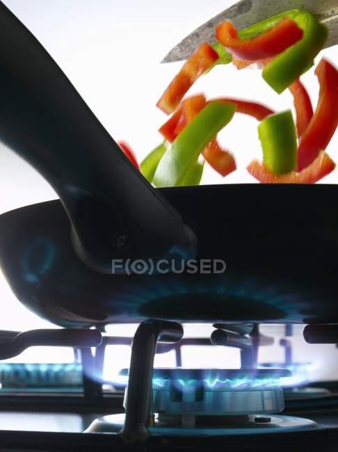Приготовление перца в сковороде на газовой плите — стоковое фото