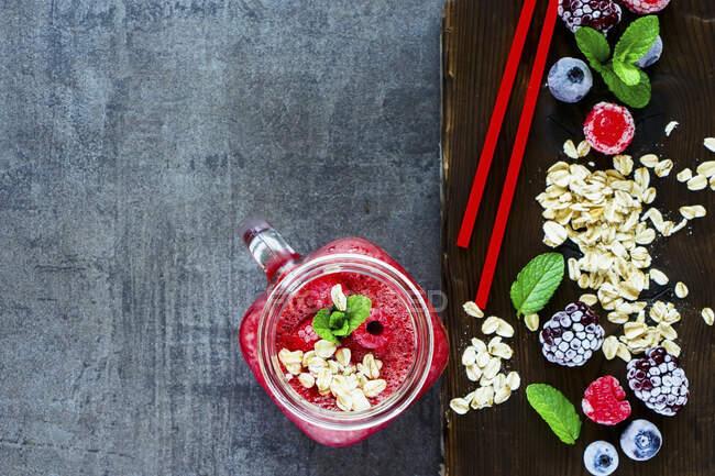 Primer plano de la bebida de batido rojo en frasco de vidrio e ingredientes saludables en la tabla de cortar oscura sobre fondo rústico - foto de stock