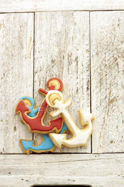 Печенье в форме якоря с красочной глазурью на деревенской деревянной поверхности — стоковое фото